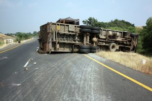 A view of an overturned truck on an highway in an accident of a person who will call a truck accident lawyer grand blanc