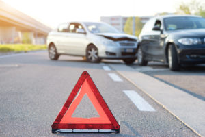 A red triangle in front of a car accident representing how our accident lawyers can help you if you have been injured