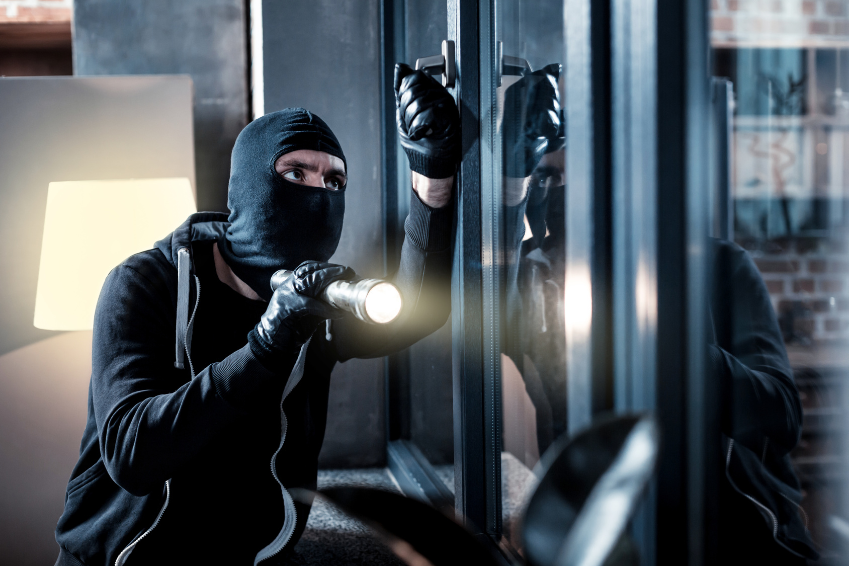 A burglar breaking into a building representing how our Michigan criminal defense attorneys can help you with your theft case