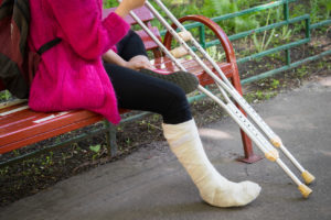 Woman sitting on a bench with a broken leg and crutches representing how if you have been injured, a Flint personal injury lawyer can assist you