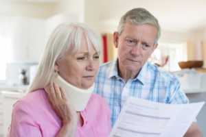 woman in neck brace looks at medical bill with husband