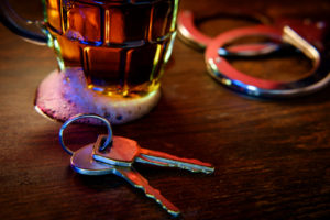 handcuffs, keys and overflowing beer mug
