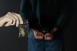hand holds bag of drugs behind man with hands cuffed behind back
