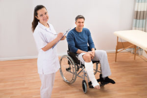 Doctor standing next to man sitting in wheelchair with leg cast
