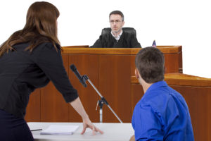 Woman talking into microphone with man in blue shirt next to her representing Criminal Defense Lawyer in Burton defending client in front of judge