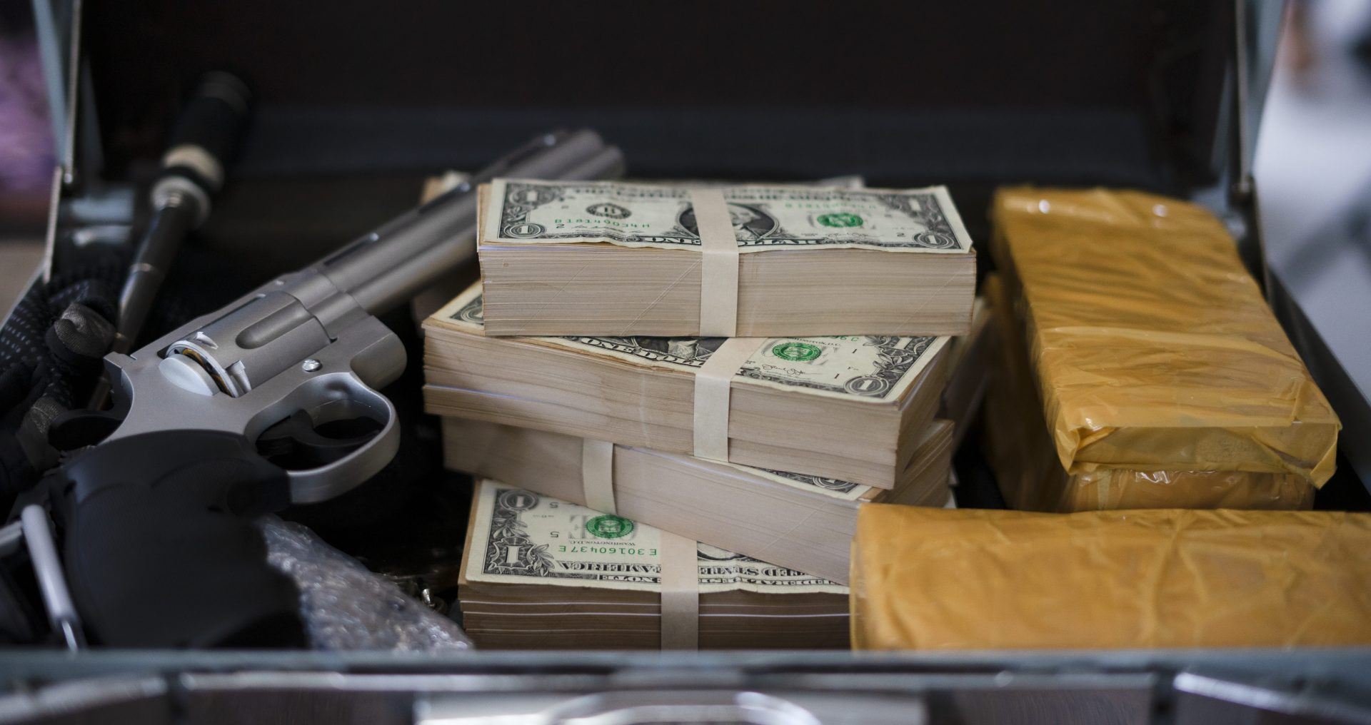 stacks of money and drugs with a gun depicting drug bust, contact our office for the best Michigan Criminal Defense Lawyer.