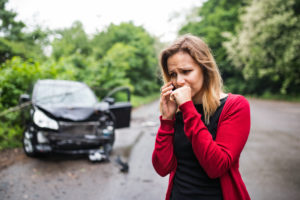 A woman on the phone after being in a wreck, if hurt it is important to speak to a Flint Auto Accident Lawyer.