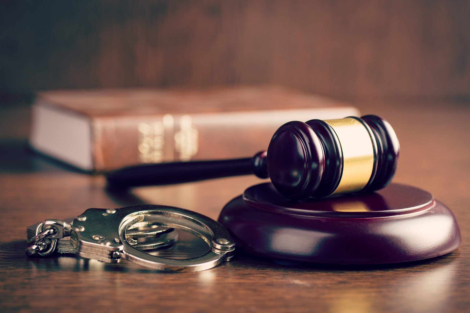 Judge's gavel and handcuffs, representing how one can benefit from contacting a Flint criminal defense lawyer.