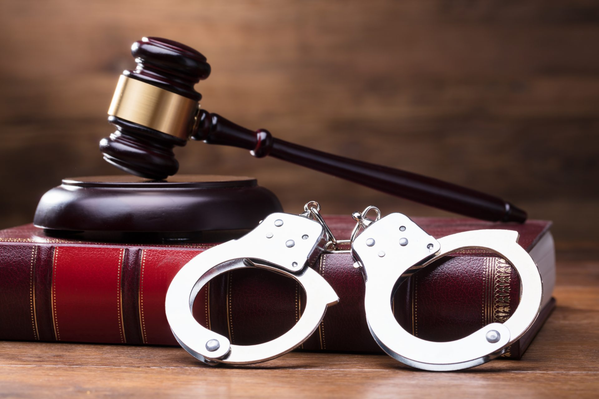 A book, a judge's gavel and handcuffs, representing how one can benefit from contacting a Flint criminal defense lawyer.