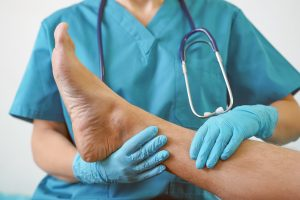Doctor examining a person's injured ankle, hire Injury Attorney Near Rankin for the best settlement.