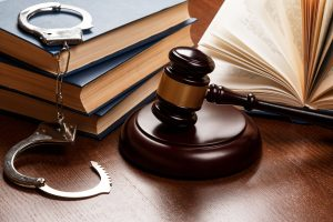 Gavel and handcuffs on table, for the best representation for your arrest see a criminal defense attorney in Clayton Township.