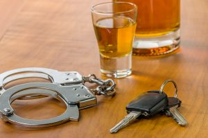Two glasses of alcohol, a set of handcuffs and car keys representing how one can benefit from calling a Grand Blanc DUI lawyer.